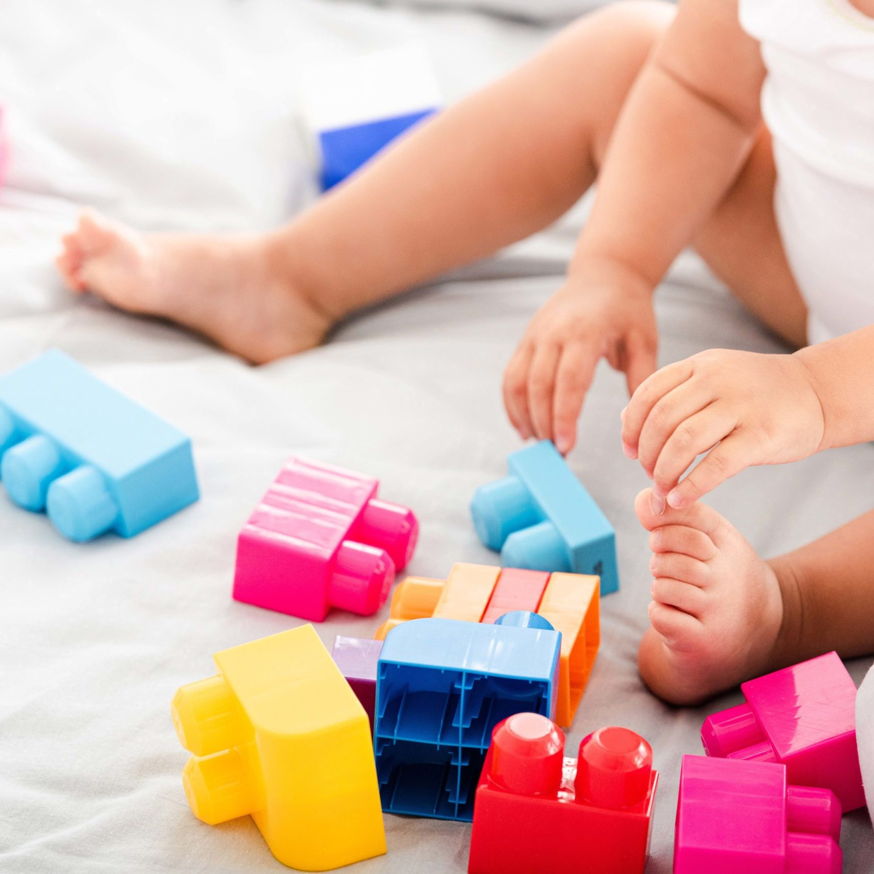 Partial view of barefoot baby in white clothes sitting on bed and playing with bright construction
